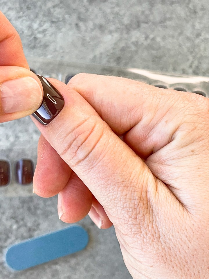 trying on press on nail sizes on thumb