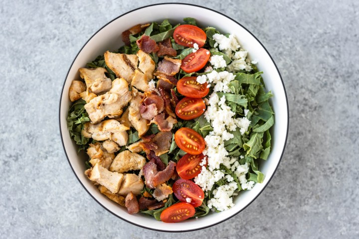 chopped kale salad with chicken, bacon, tomato and feta