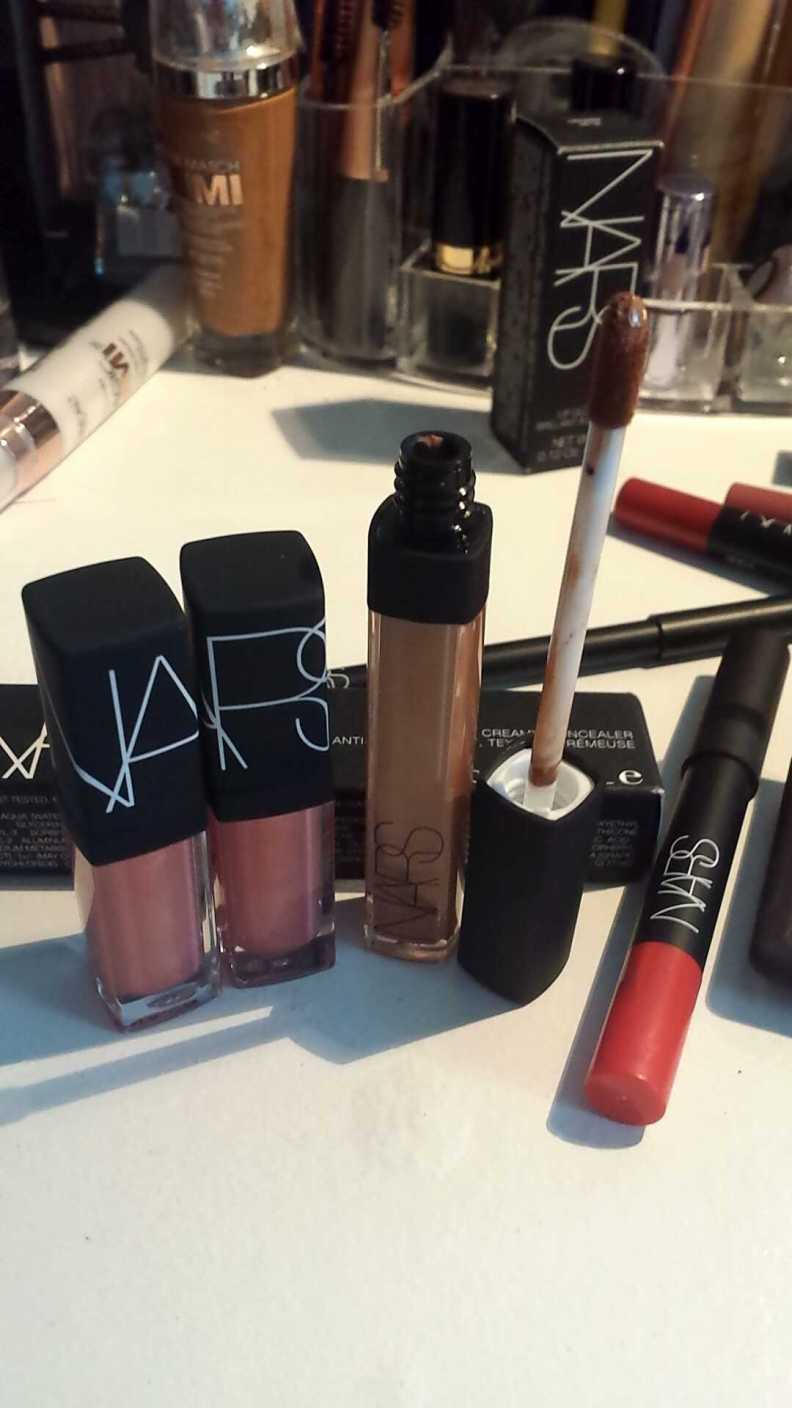 NARS Radiant Creamy Concealer placed beside NARS Orgasm lip glosses (miniature sizes) for reference