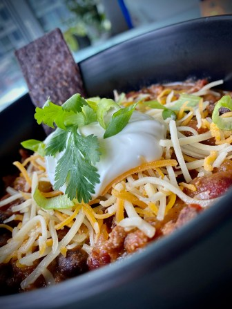 It's CHILI SEASON! And this is the, hands-down BEST bowl of chili ever -- because it includes BACON!! It's gluten free and the perfect comfort food! Bring on the fall! #food #recipe #chili #football #glutenfree #keto #paleo #healthyfood #bacon #cooking