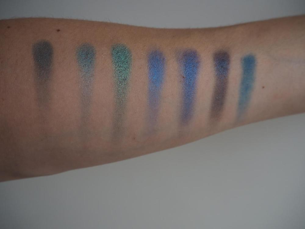 Row of eyeshadow swatches on my arm from row 2 of Morphe 35d palette blues and greens