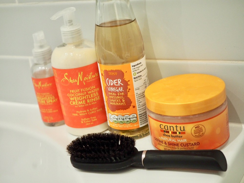 How To Transition From Shampoo To No Poo- a brush, a bottle of vinegar and a conditioner