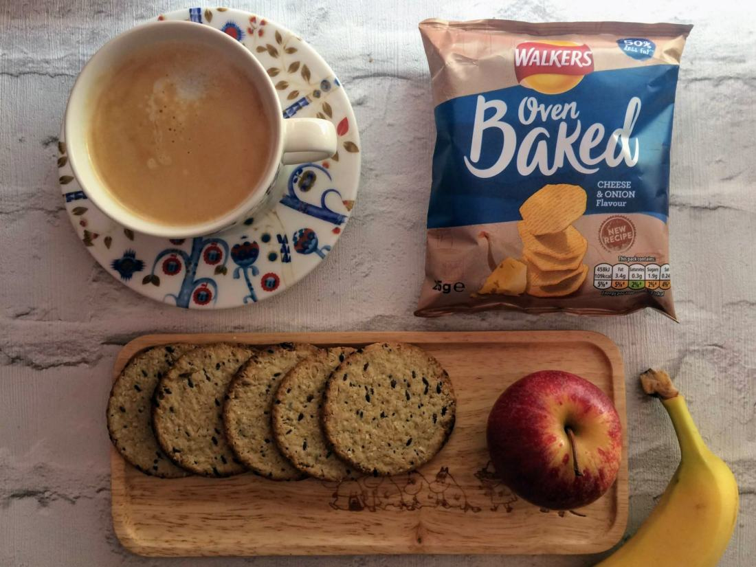 coffee cup and saucer, oatcakes on a tray with apple, packet of crisps