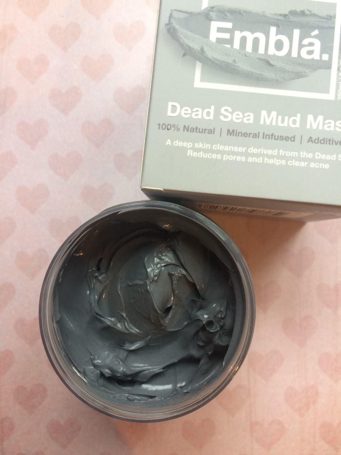 Jar of mud mask with lid off showing contents and grey colour