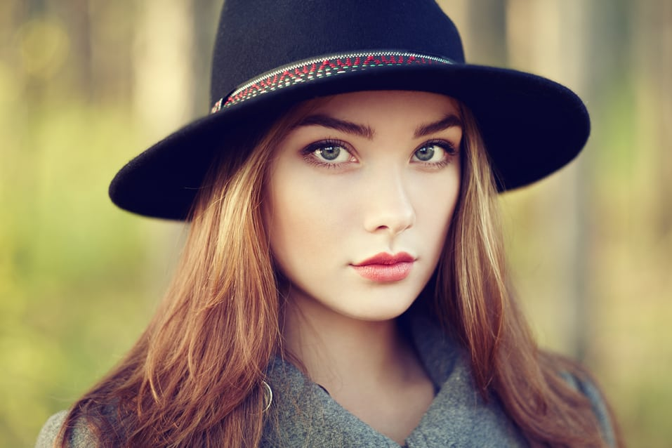 Portrait of young beautiful woman in autumn coat. Girl in hat. Fashion photo. Are you SunSmart?