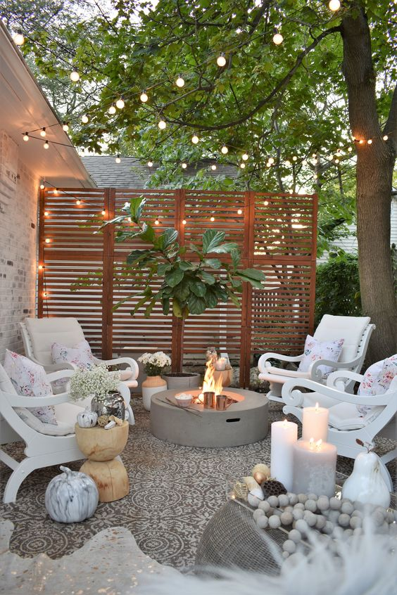 A farmhouse style cozy patio with a firepit and marketlights.