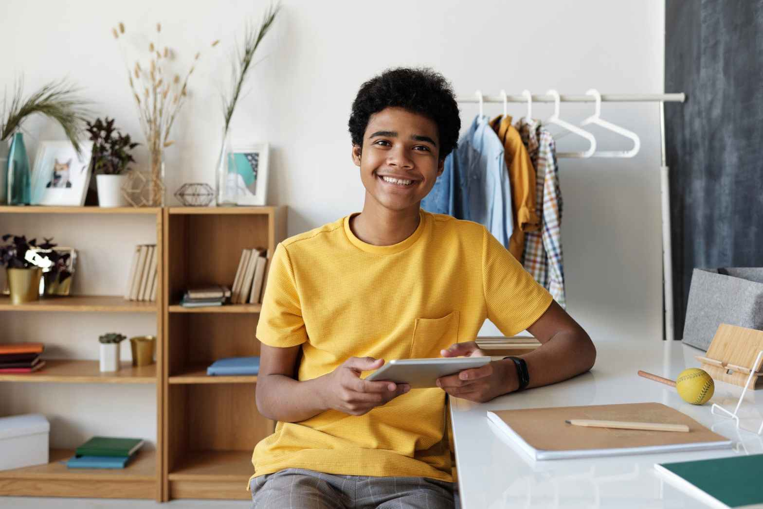 boy in yellow crew neck t shirt sitting on chair