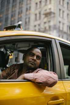 man in black and white striped shirt sitting inside yellow car