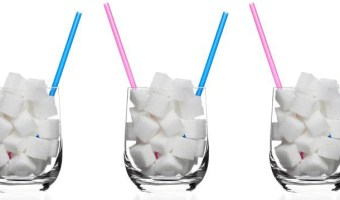 white sugar cubes in a clear glass with pink straws and blue straws