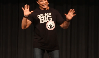Marc Mero on stage with a black shirt and white writing talking about his mom