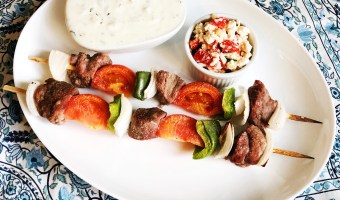 greek food beef kabobs plated with alove greek yogurt taziki sauce with feta cheese and tomato on a blue flower table cloth
