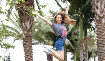 saarah wassel samadani jumping for joy in front of los angeles palm trees. celebrating success of vaginal rejuvenation with vconfidence and viveve.