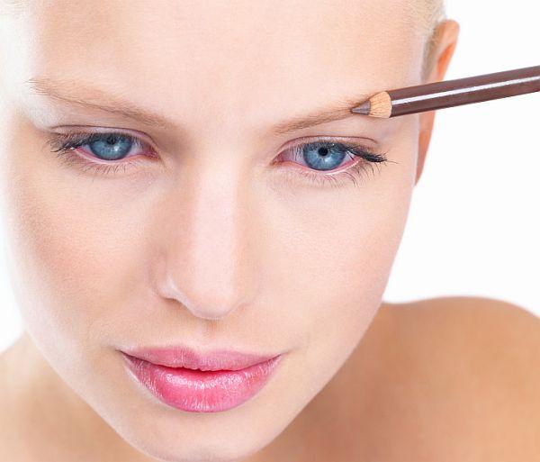 Young woman applying eyebrow pencil