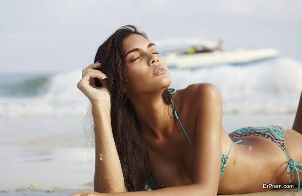 Asian fashion model in bikini on the sea coast