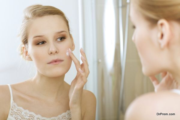 Young woman applying beauty cream, close up