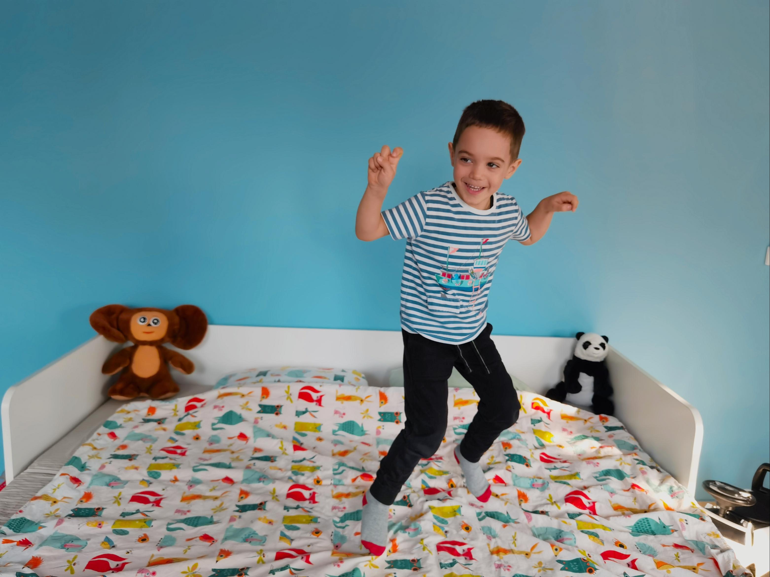 Дете скача върху легло