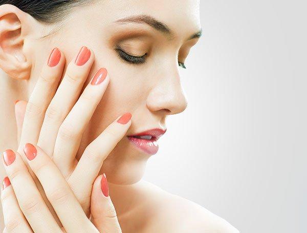 dłonie kobiety z pomarańczowymi paznokciami