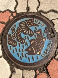 Lovely fish on man hole cover near Yoko Saito's shop