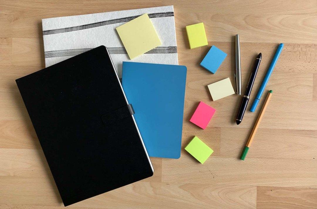 Drei verschiedene Notizbücher, farbige Klebezettel und vier Stifte