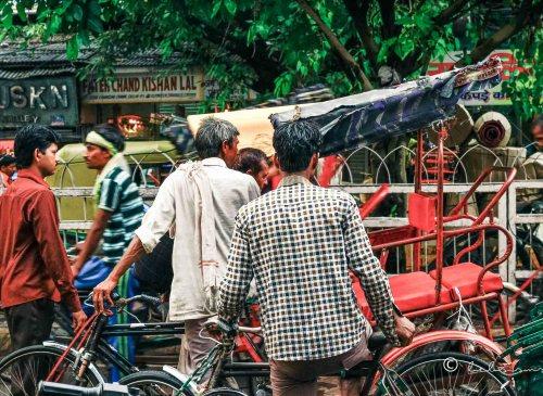 indian men riding their rickshaws