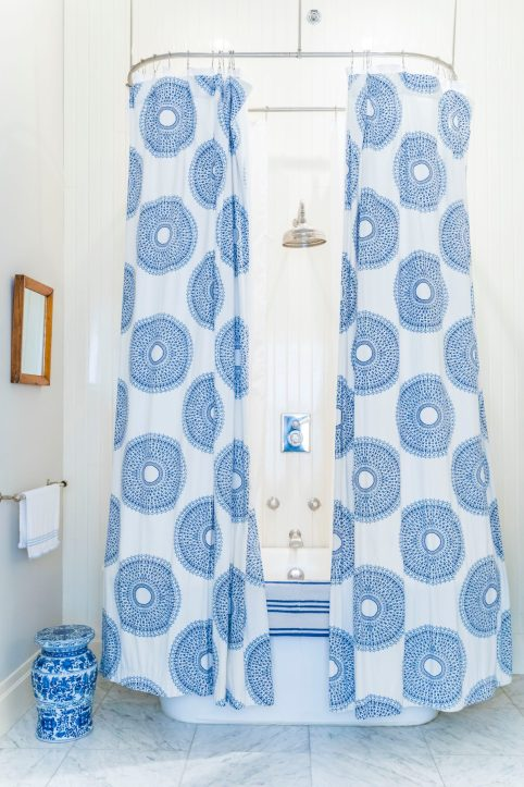 Photo of a bathroom shower with a blue and white curtain