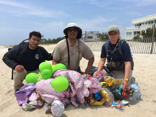 Three people on a beach with over 100 collected balloons found during a beach clean-up.
