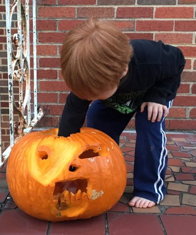 Child placing a candle inside of a Jack O' Lantern