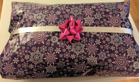 I wrapped the pillow up for Christmas. (We are using up the gift paper and ribbon we have and then moving to homemade or reused wrapping paper. I did use recyclable paper tape on this gift.)