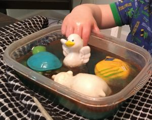 """My son experimenting with toy animals in the """"oil spill."""""""