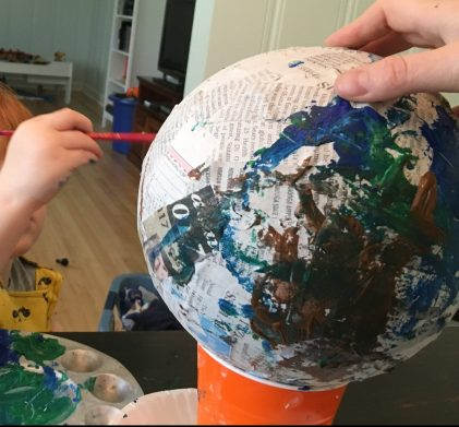 My son painting our paper mache Earth.