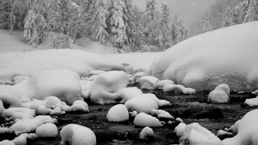 Black and white photograph of a snow covered creek. Photo by Tono Graphy on Unsplash