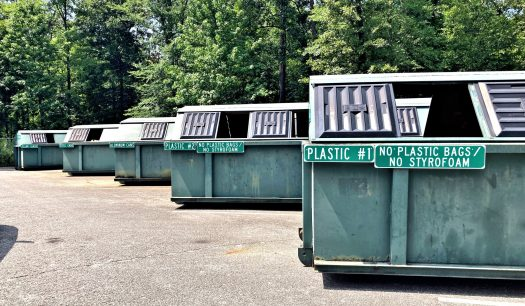 Dark green recycling containers at the Access Road center. Each are labeled with signs for plastic, aluminum, steel cans, and glass.