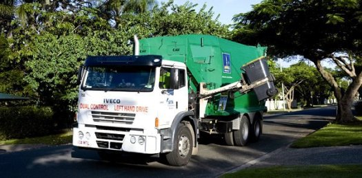 Green and white recycling truck on street, using a the lift to dump a residential recycling bin on a street.