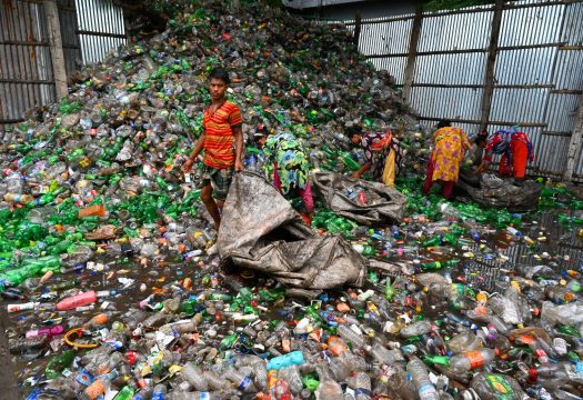 People sorting recycling in standing filthy water in Bangladesh.