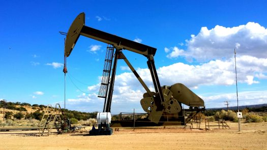 Oil pump with bright blue sky and white clouds background