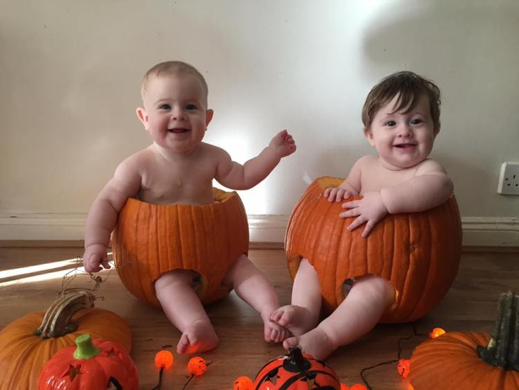 Twins sitting in pumpkins