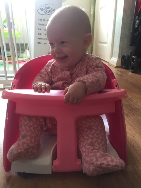 smiling baby girl, sitting in a pink and white bath chair