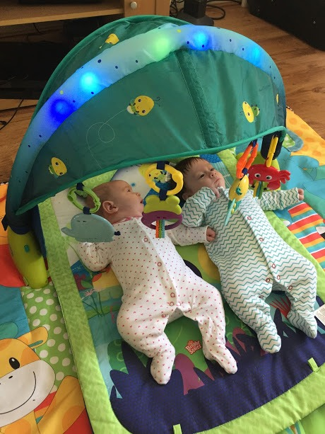 Baby twins laying on a play mat with a light up archway over it