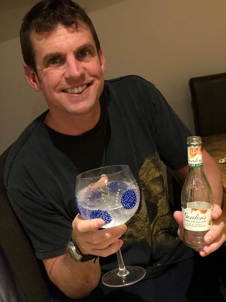 smiling man with bottle of G and T flavoured drink