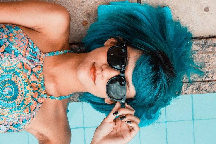 woman with blue hair and sunglasses, laying on back by pool