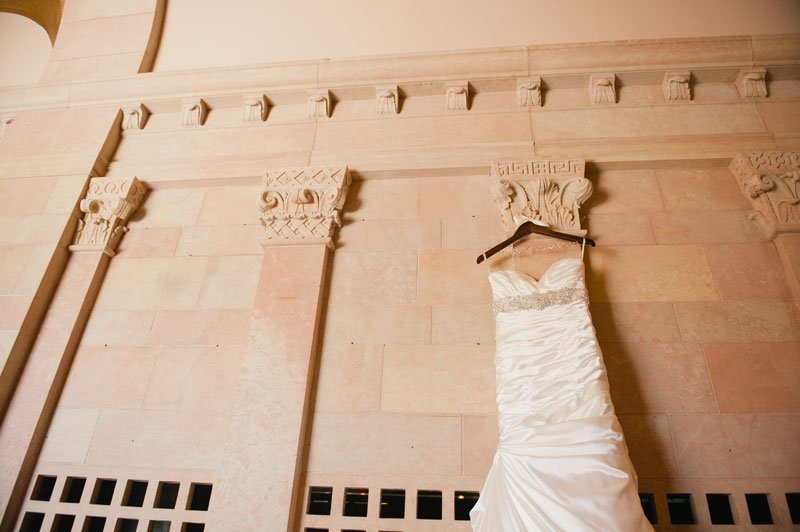 wedding dress hanging on stone architecture of St Thomas More Catholic Church in St Paul, MN