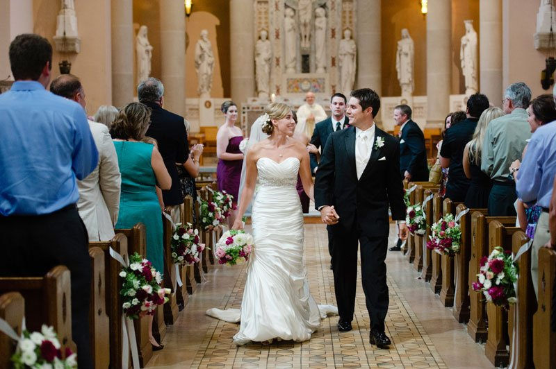 bride and groom walk down aisle at St Thomas More Catholic Church in St Paul, MN