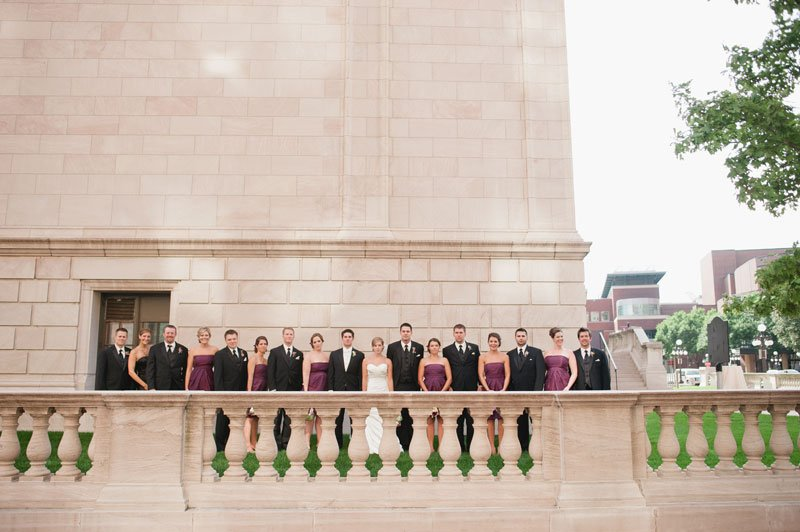 large wedding party with stone architecture in Rice Park, St Paul