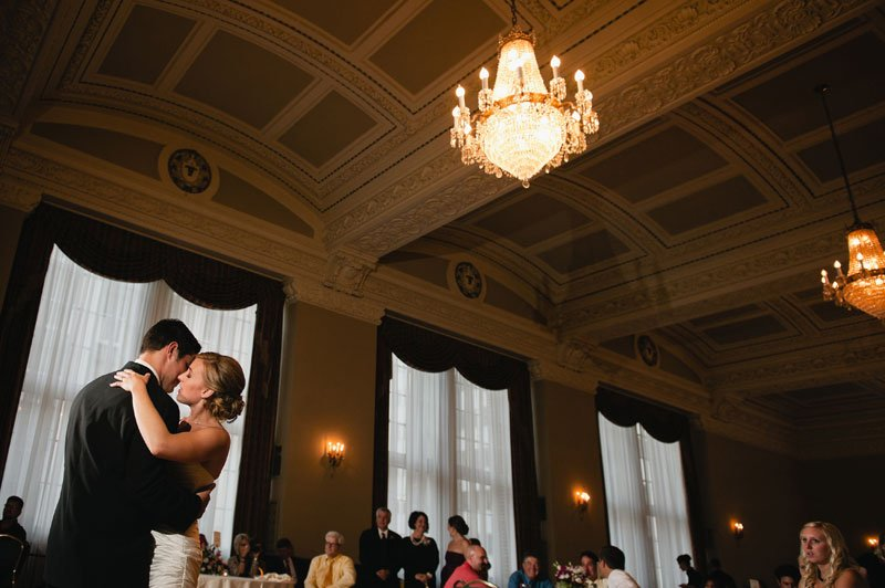 bride and groom kiss during first dance with chandelier at University Club and Hotel 340 Wedding in St Paul, MN