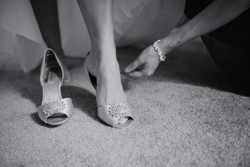 detail of bride getting shoe on