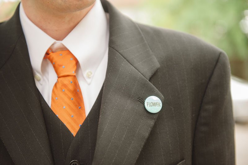 """groom's boutonniere is a pin that says """"flower"""""""