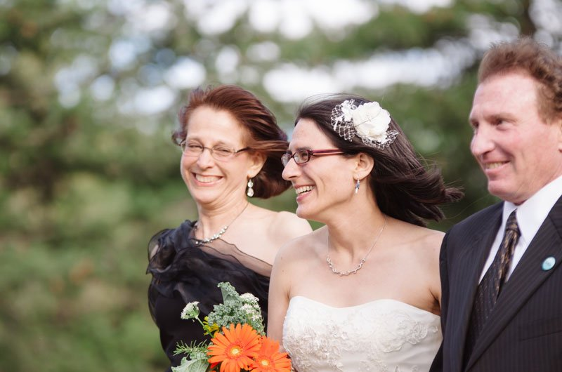 bride walks to wedding ceremony with parents at Lake Hiawatha