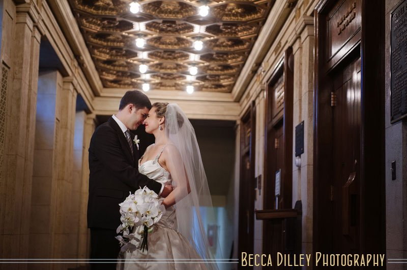 bride and groom under antique architectural lighting of Temple Israel in Minneapolis jewish wedding