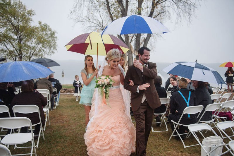 bride and groom walk down aisle for rainy day wedding on stillwater mn peninsula