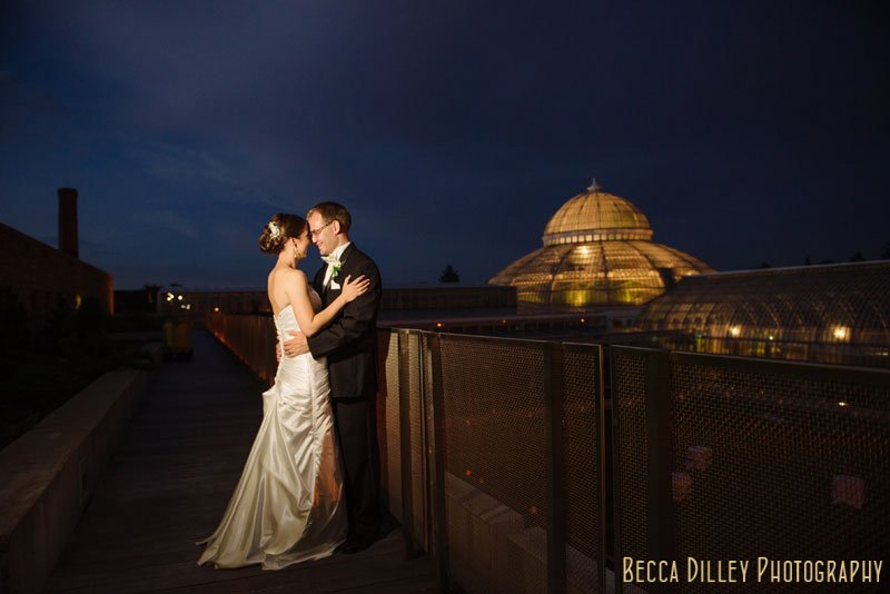 mn wedding photographer bride and groom at night in front of lite up conservatory dome at como park st paul